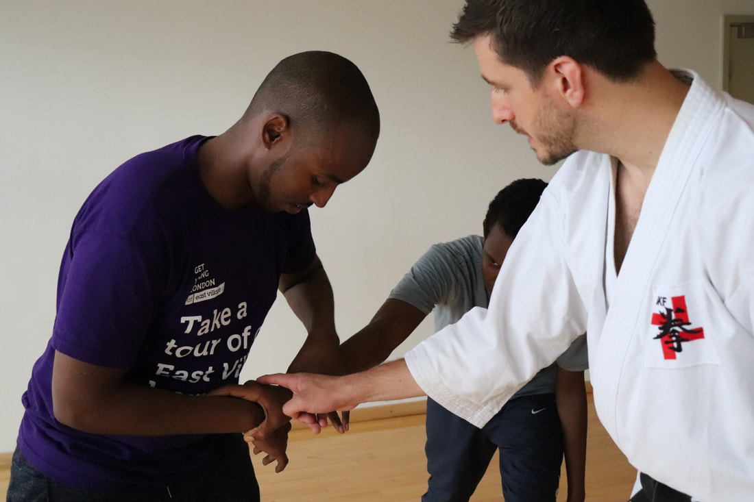 Two students learning one of Shorinji kempo's self-defence techniques